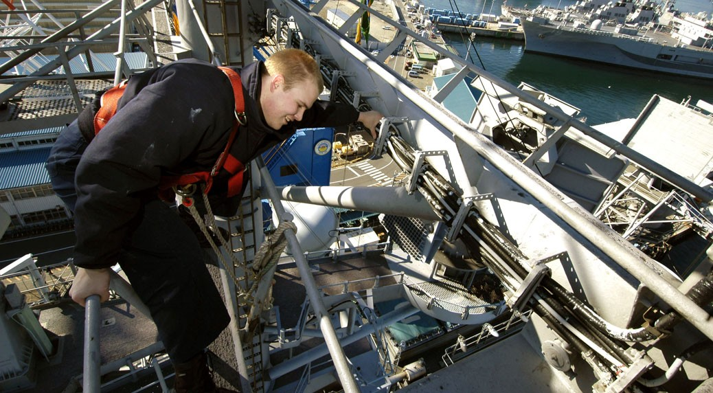 051220-N-9389D-092 YOKOSUKA, Japan (Dec. 20, 2005) - Quartermaster Seaman Matthew Lenerville of Dickenson, N.D., secures a safety line on railing while working aloft to hang Christmas lights on the mast of USS Kitty Hawk (CV 63). Currently in port, Kitty Hawk demonstrates power projection and sea control as the U.S. Navy's only permanently forward-deployed aircraft carrier operating out of Yokosuka, Japan. U.S. Navy photograph by Photographer's Mate Airman Benjamin Dennis